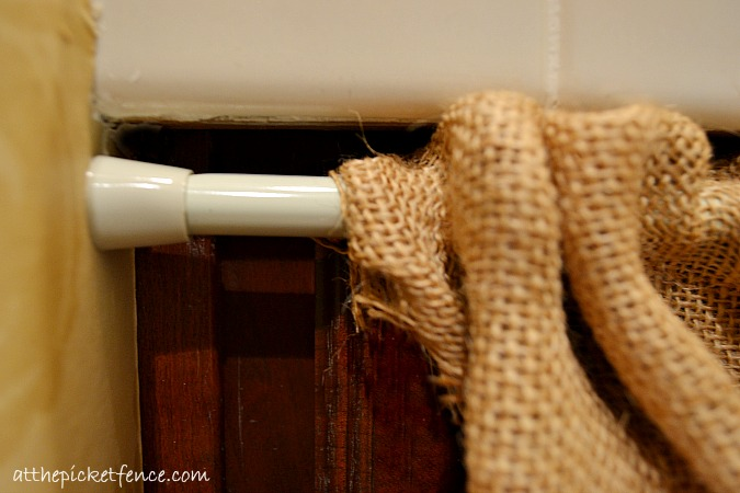 use a tension rod for burlap vanity skirt at the picket fence