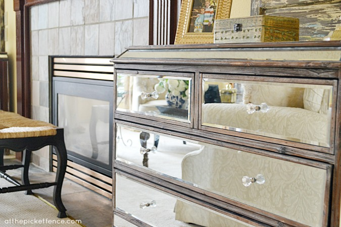 Mirrored dresser next to fireplace www atthepicketfence com