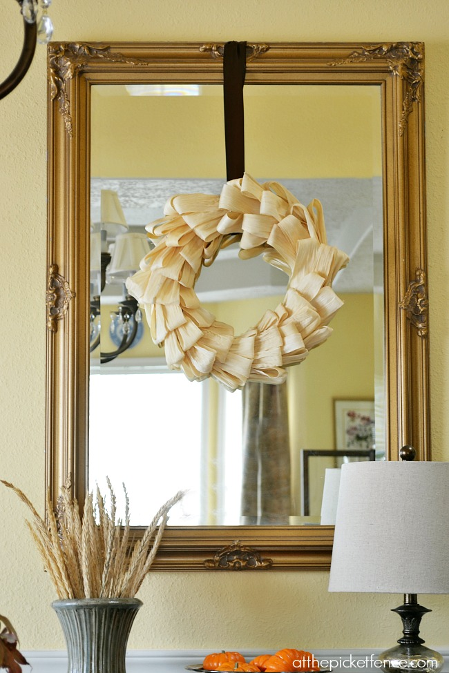 Corn husk wreath hanging on mirror from atthepicketfence.com