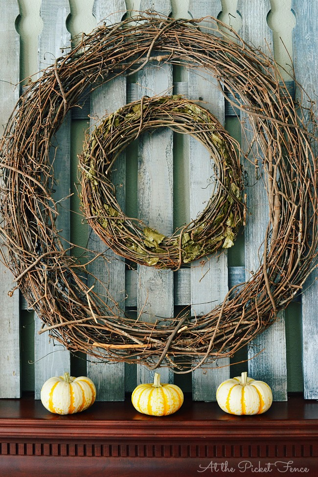Double grapevine wreath on a picket fence for simple fall mantel decorating