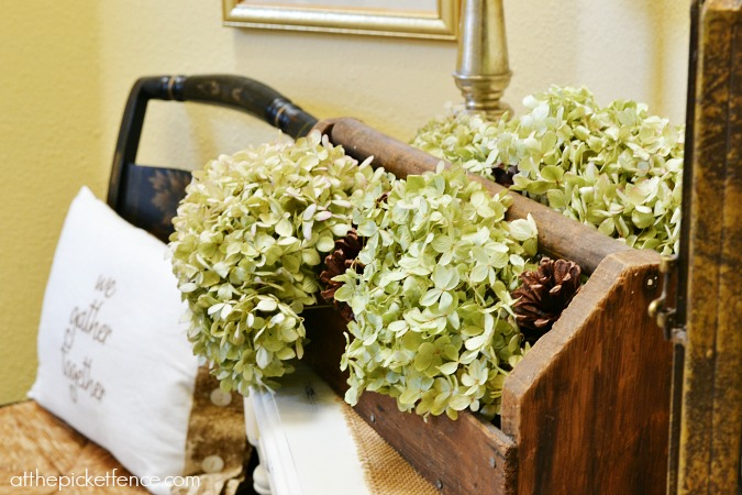 Hydrangeas and pine cones in a vintage toolbox for easy autumn decor from atthepicketfence.com