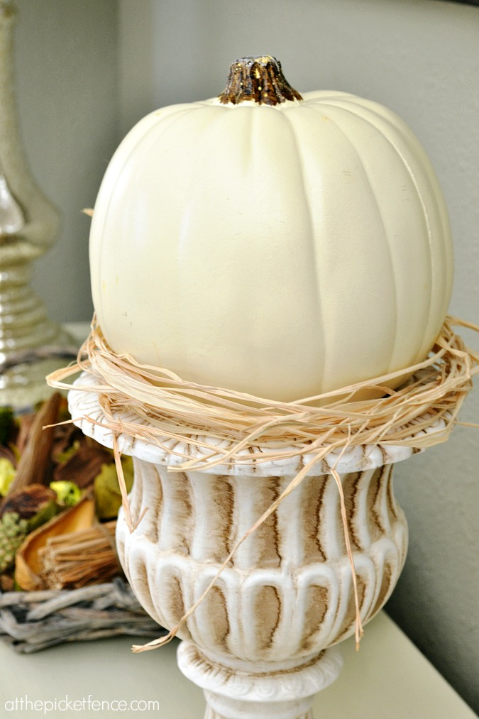 White pumpkin in urn with raffia from atthepicketfence.com