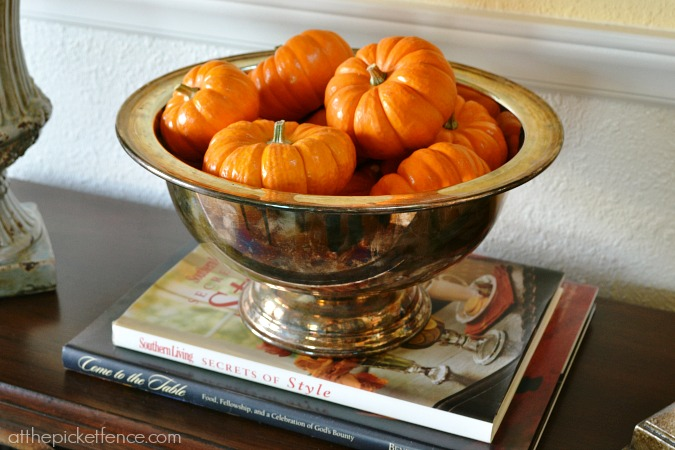 Orange pumpkins in silver bowl from atthepicketfence.com