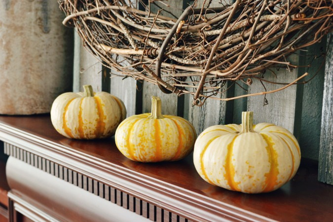 Trio of pumpkins on fall mantel from atthepicketfence.com