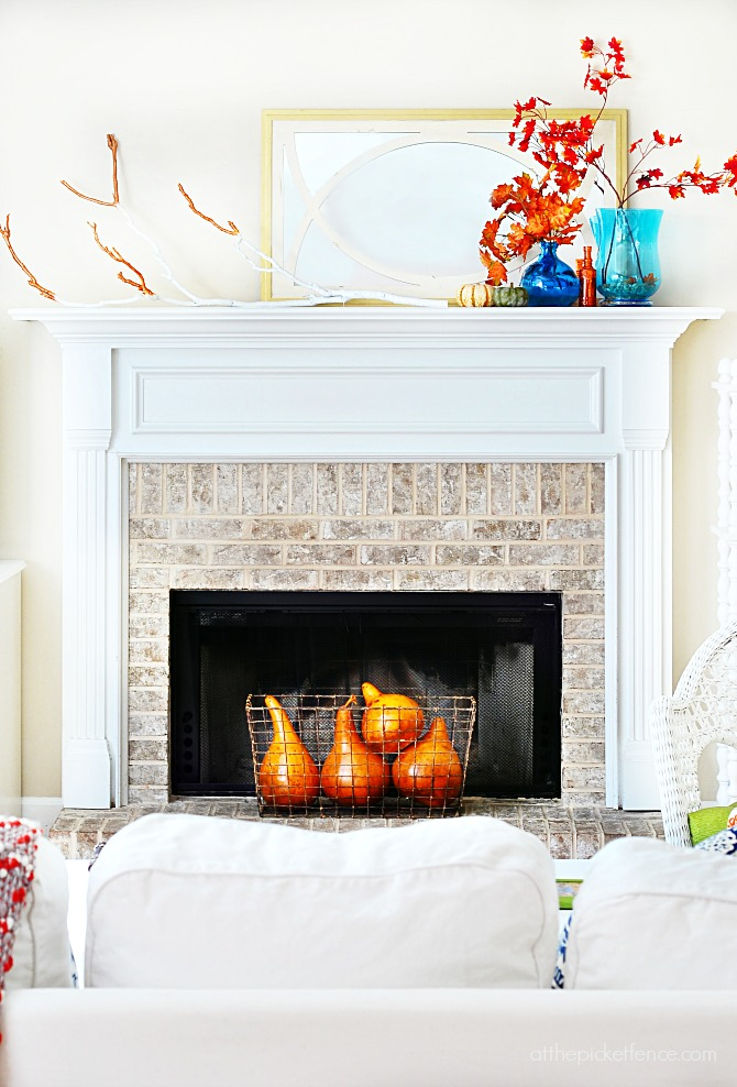 simple fall mantel with maple leaves and painted branch