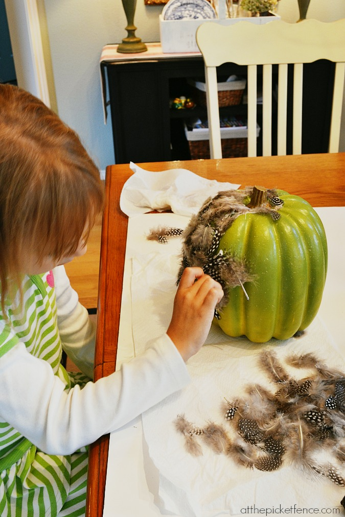 putting feathers on pumpkin