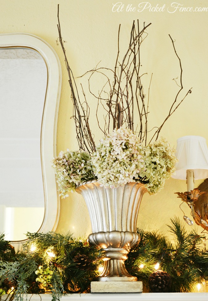Branches and dried hydrangeas in urn on mantel from atthepicketfence.com