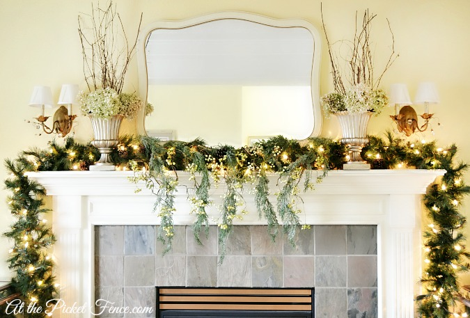 Christmas mantel with branches and dried hydrangeas in urns from atthepicketfence.com