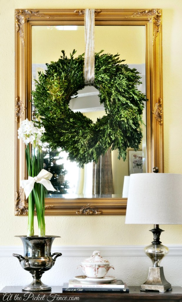 Mirror with boxwood wreath and paper whites in silver urn from atthepicketfence.com
