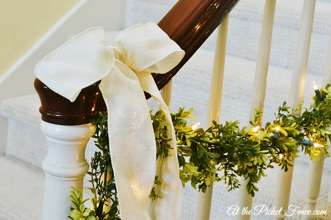 cream bow with boxwood garland on banister from atthepicketfence.com