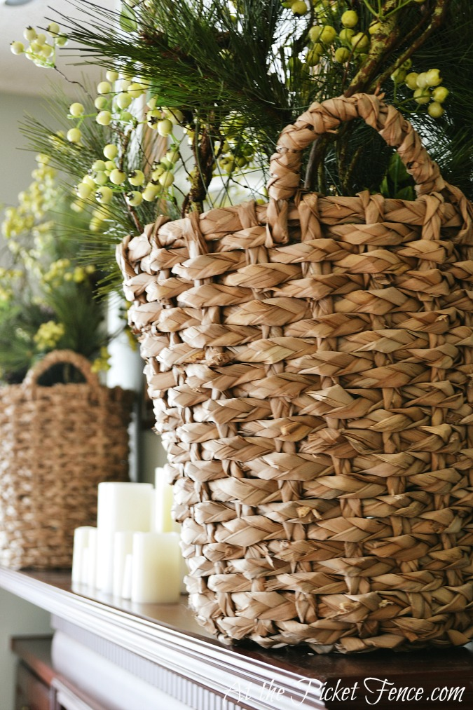 winter greenery and berries in baskets on mantel