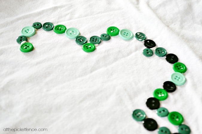 gluing buttons onto shamrock shirt
