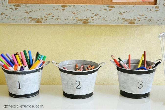 numbered galvanized buckets holding art supplies