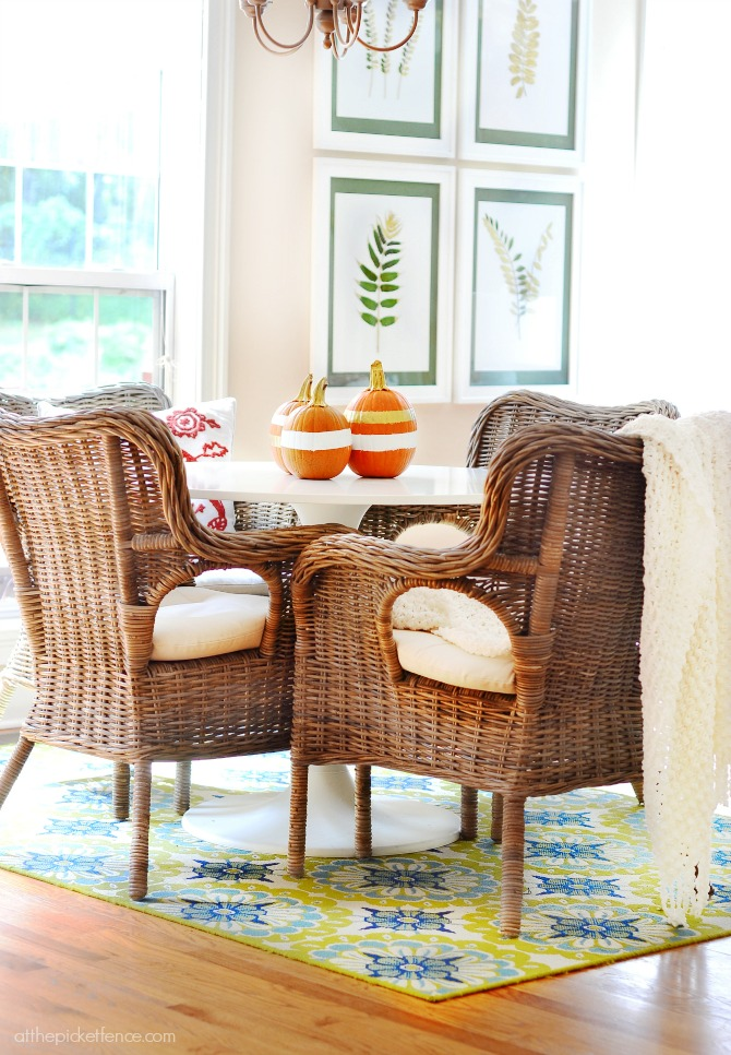 rattan chairs and tulip table with gold and white pumpkins