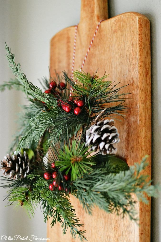 Christmas greenery hanging on wood cutting board atthepicketfence.com
