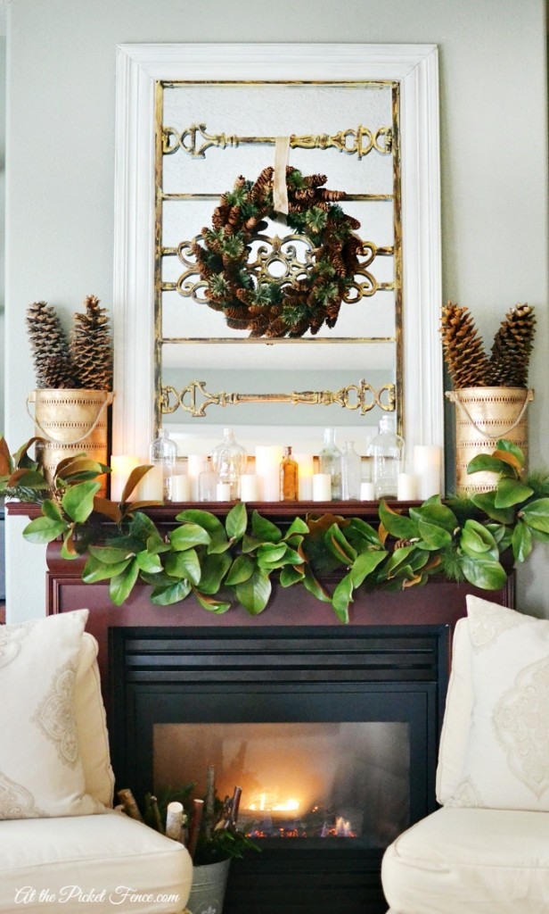 Christmas mantel with magnolia garland bottles and candles atthepicketfence.com
