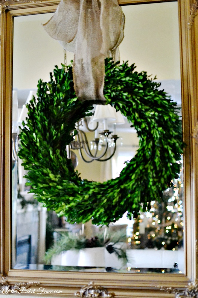 boxwood wreath hanging on mirror with burlap ribbon atthepicketfence.com