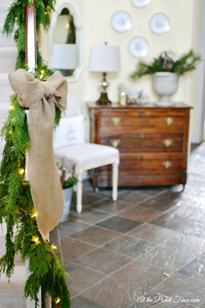 fresh greenery on staircase with burlap bow atthepicketfence.com