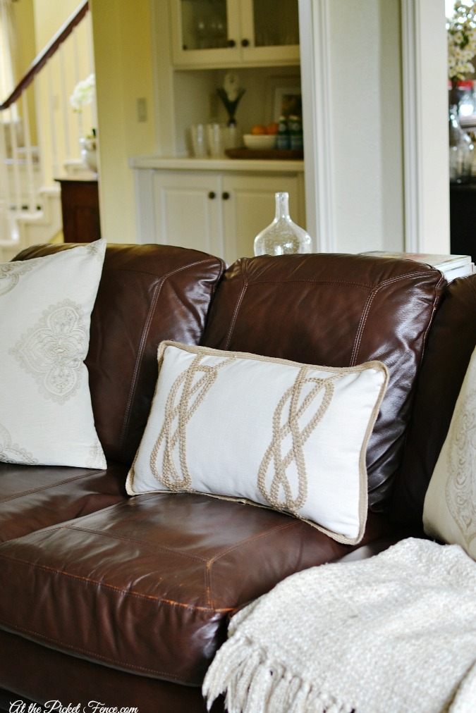 Leather couch with cream pillows atthepicketfence.com