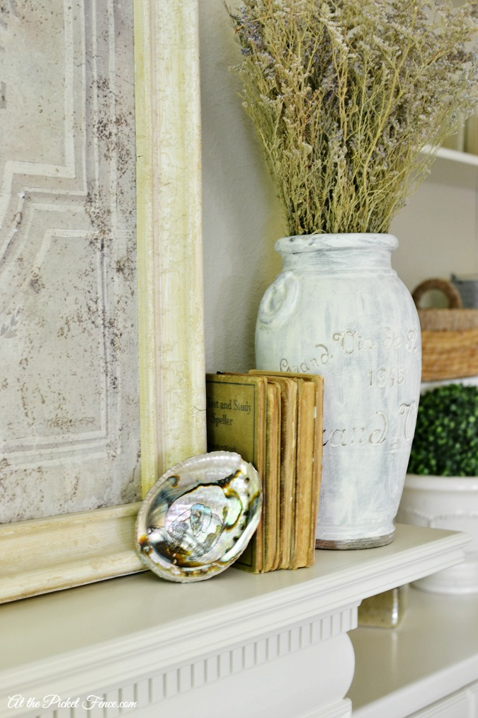 seashell and vintage books on mantel