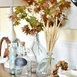 Fall buffet table decor with glass bottles and leaves atthepicketfence.com