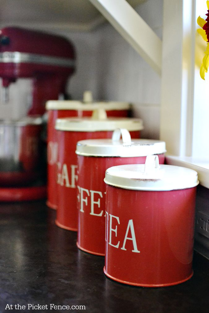 Red tin canisters in kitchen atthepicketfence.com