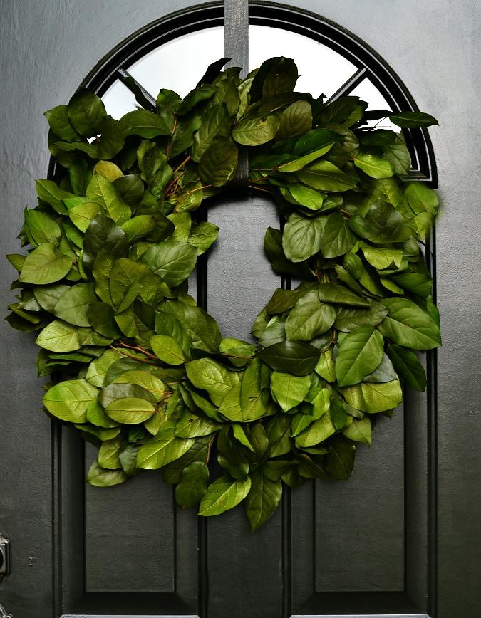 green wreath on black front door atthepicketfence.com