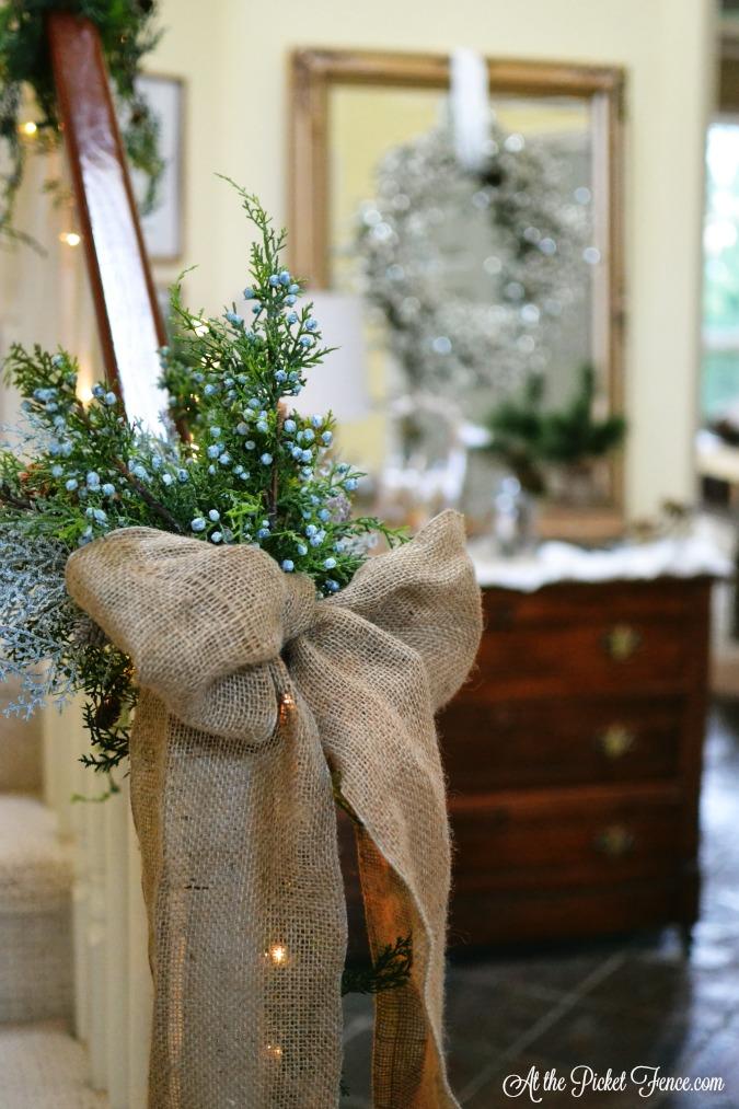 greenery spray on banister for Christmas