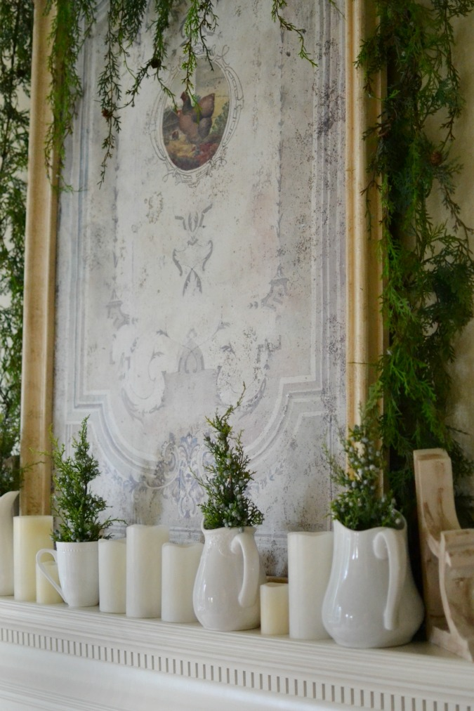 Christmas mantel with white pitchers and greenery