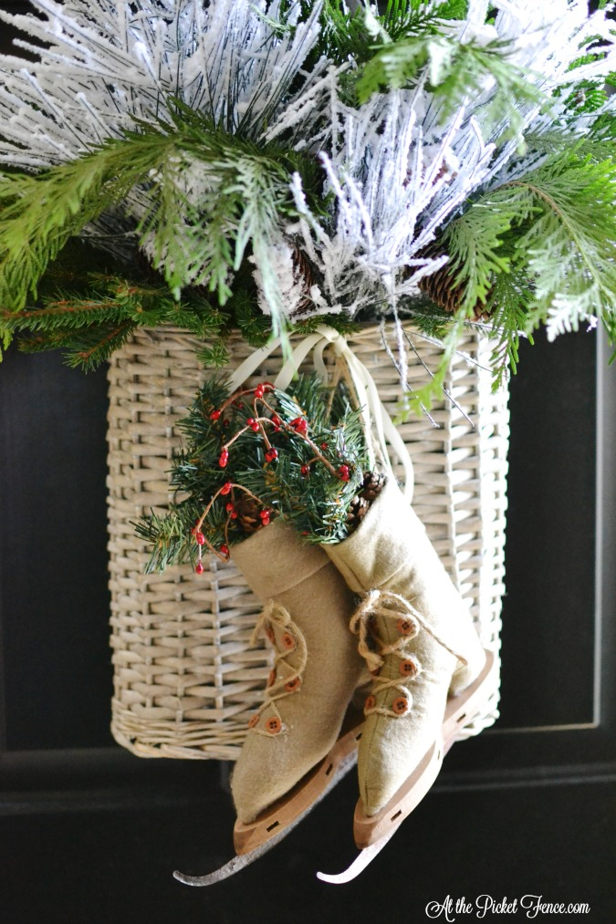 Front door basket with greenery and ice skates atthepicketfence.com