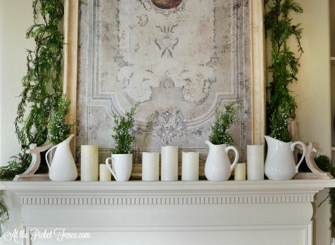 Winter mantel with white pitchers and greenery atthepicketfence.com