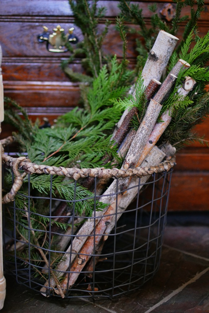 branches and greenery in metal basket
