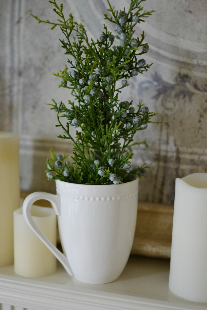 greenery in white cup on mantel