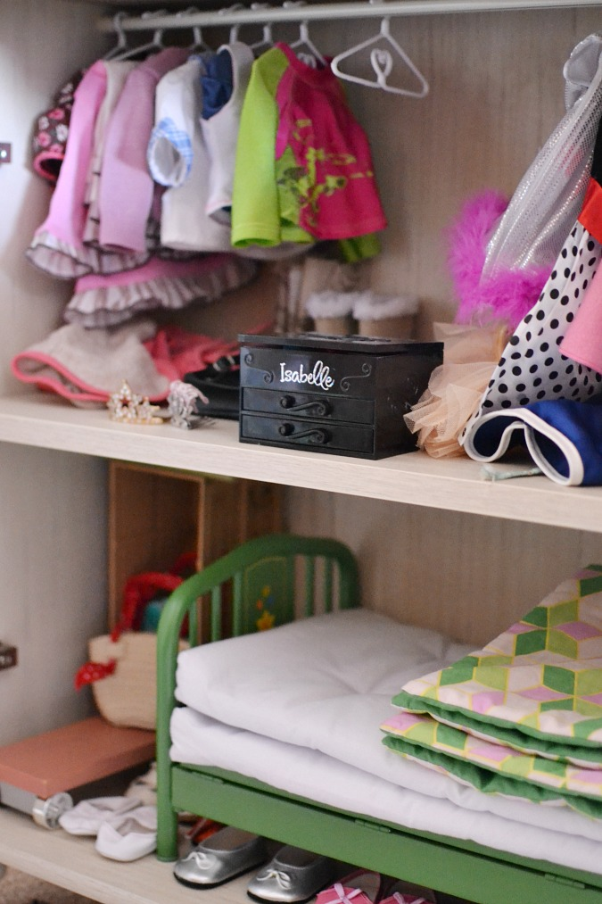 Doll closet inside a cabinet using a tension rod