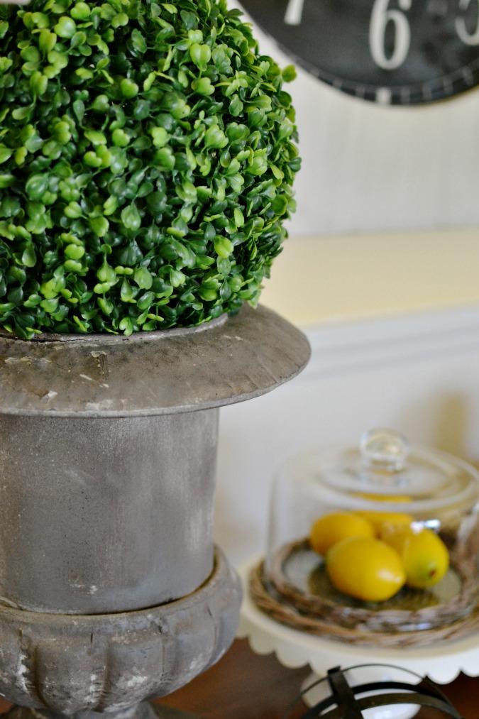 Green topiary ball in metal urn