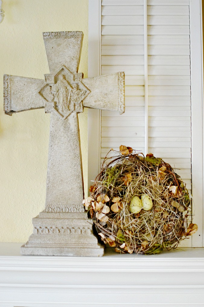 Stone cross and birds nest on Easter mantel