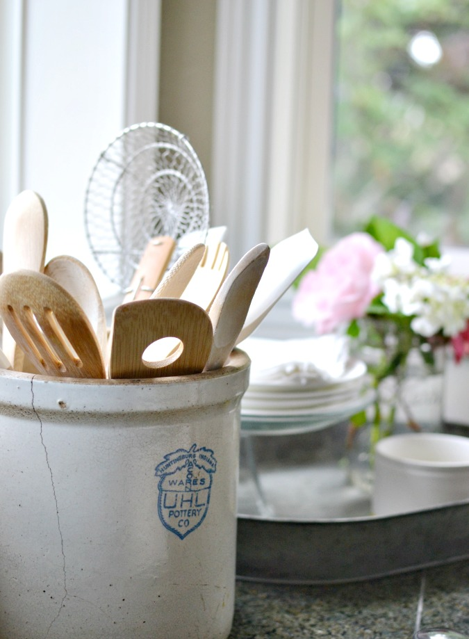 stoneware crock holding wooden spoons