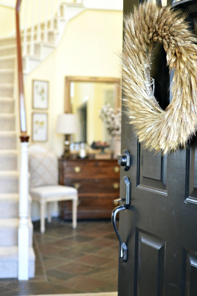Black front door with wheat wreath atthepicketfence.com