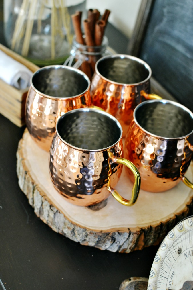 Copper mugs on a wood round atthepicketfence.com