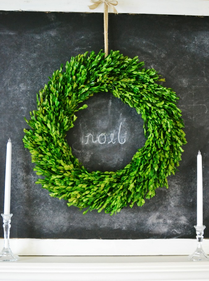 Boxwood wreath hanging on a chalkboard atthepicketfence.com