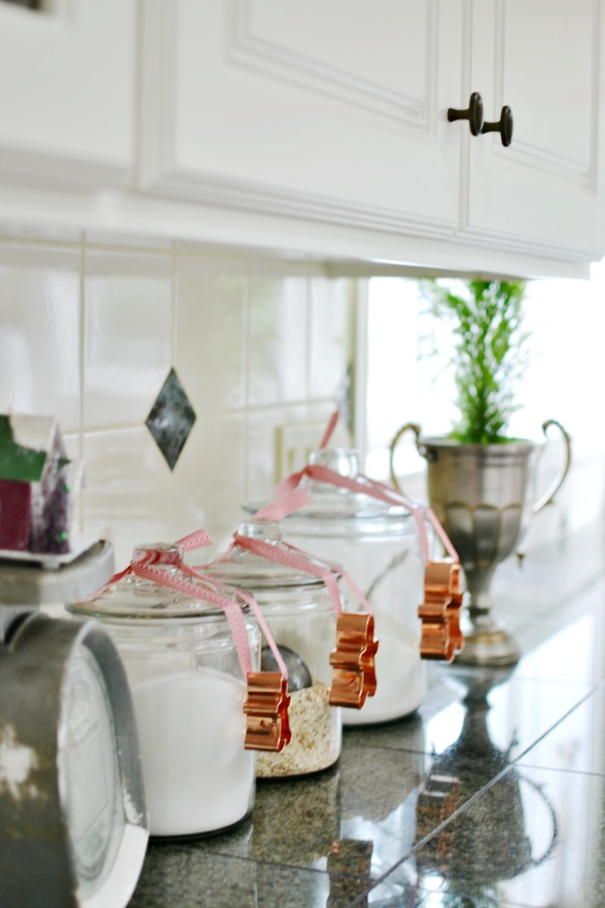 Gingerbread men cookie cutters tied to canisters in Christmas kitchen