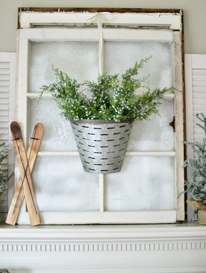 Vintage windows with faux snow on mantel atthepicketfence.com