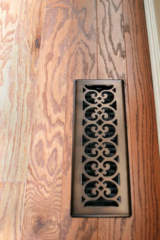 Scroll metal vent cover on hardwood floor