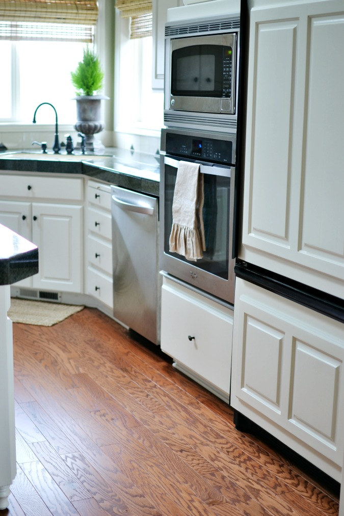 white kitchen cabinets with cherry hardwood floors atthepicketfence.com
